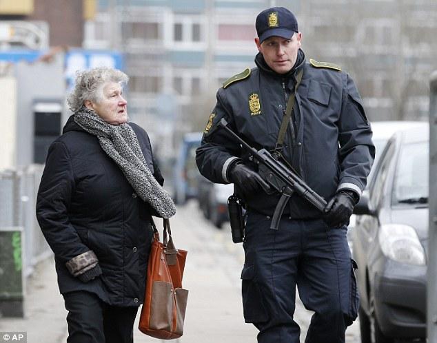 Un anciano residente está acompañado por la calle en Norrebro donde mataron al sospechoso fuera de una estación de metro en la madrugada