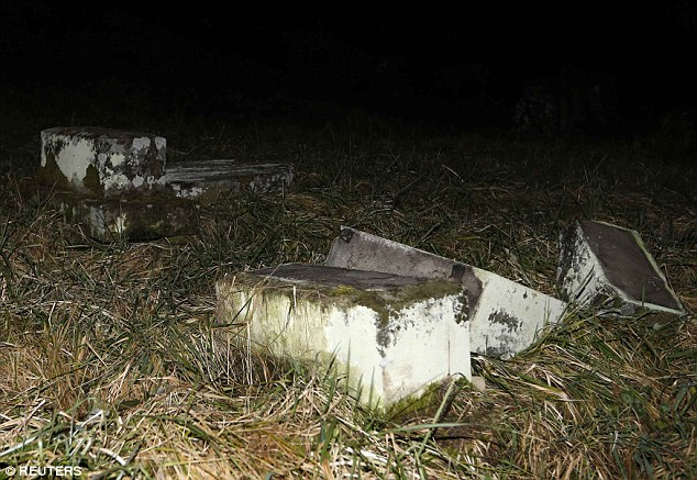 Shocking scene: Up to 400 gravestones were vandalised by being kicked over, or had Nazi swastikas daubed on them in red paint