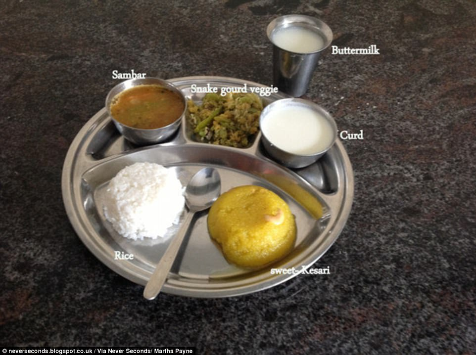 South Indian school children eat off a thali plate which has white rice, sambar (dhal), smoked gourd vegetable stir-fry, curd, buttermilk and kesari, a type of sweet dessert made from semolina