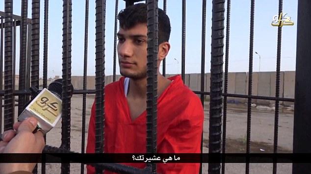 Un joven prisionero encadenado es visto entrevistado por un militante cuyo micrófono osos insignias asociado con el grupo terrorista