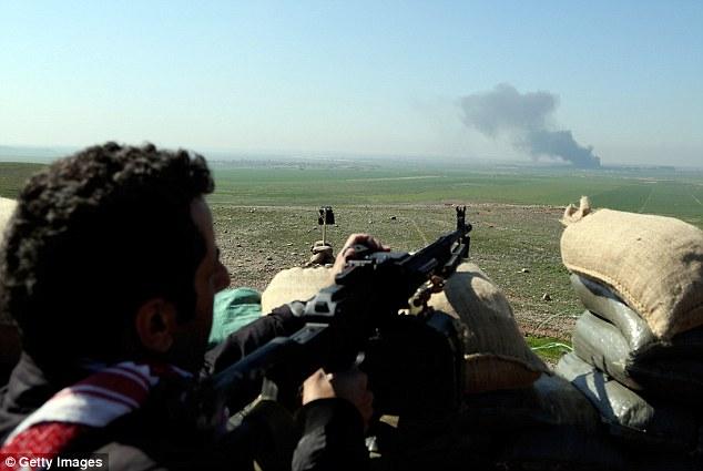 Preparativos: Un combatiente kurdo pretende como islamistas queman neumáticos en la distancia a oscurecer su campo de visión