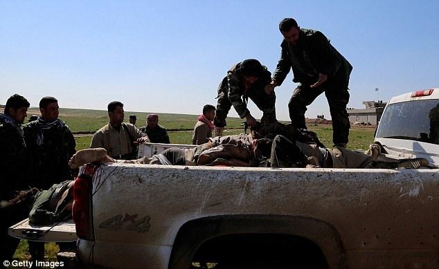 Trabajo Grim: Los cuerpos de los hombres estaban apilados en un camión de cama plana por las fuerzas kurdas peshmerga hoy