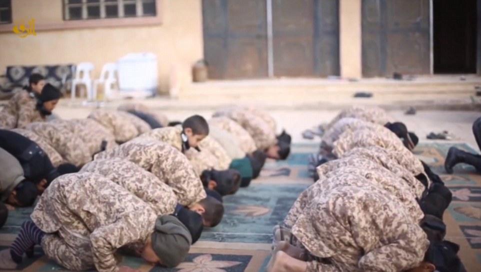 A los niños se ven orando y recibiendo clases en árabe, pero el campo es también donde los niños se están preparando para la batalla