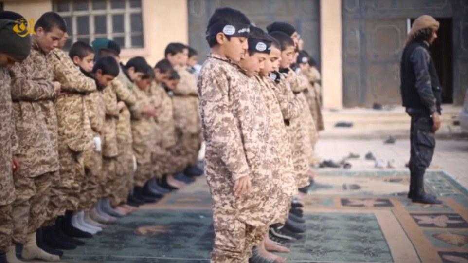 Los chicos realizan oraciones, todavía vestido con uniforme de camuflaje y algunos todavía usan bandanas teniendo insignias asociado con el grupo