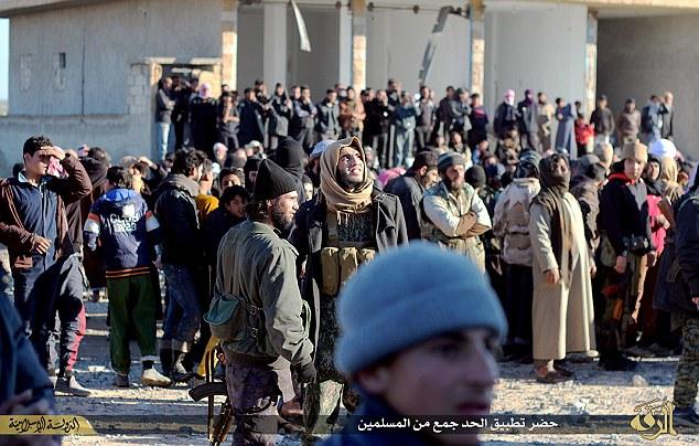 Teniendo testigo: Una gran multitud de combatientes y residentes locales de Raqqa es mostrado reuniendo para ver el castigo horrible fuera del edificio de la corte islámica en Tal Abiad.