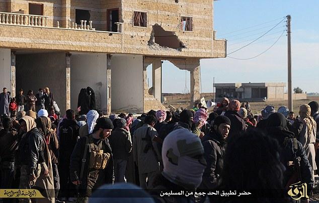 Ocultos a la vista: Tres mujeres vestidas niqab se le ve a la espera de la sanción que se llevarán a cabo.  Las mujeres rara vez son vistos viendo ejecuciones públicas en el territorio del Estado islámico.