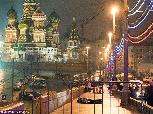 Leading Russian opposition politician Boris Nemtsov was shot dead on a bridge in central Moscow at just after midnight on Friday, pictured (centre) is a body bag with Saint Basil's Cathedral in the background