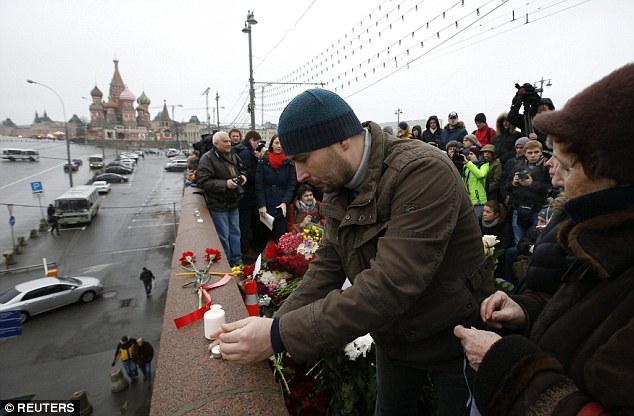 La gente enciende velas y flores en el lugar donde Nemtsov fue baleado ponen al caminar a través de un puente sobre el río Moscova