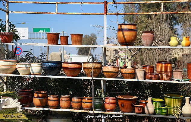 Empty clay plant pots, some decorated with Arabic inscribed patterns are shown sitting neglected on a stack of shelves.