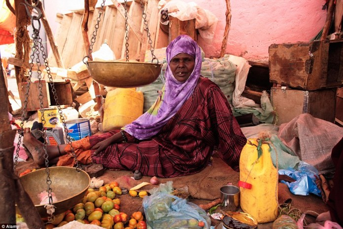 A woman sits among her scales awaiting her next sale of vegetables in the market in Hargeisa, a city in the northwestern Woqooyi Galbeed province
