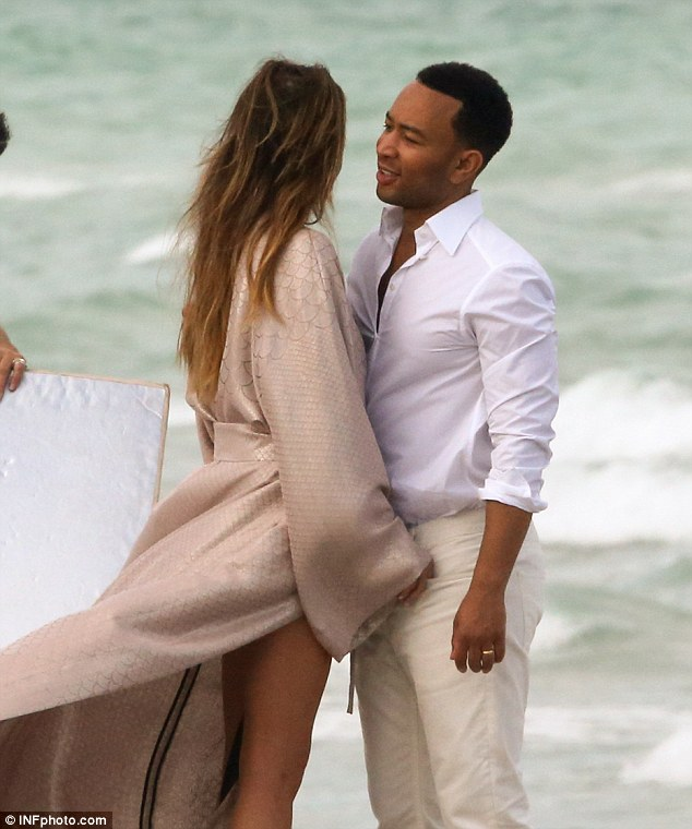 Windy day: Thanks to the blustery conditions on the idyllic beach, the model beauty's legs were on full display as her kimono-style robe blew around her