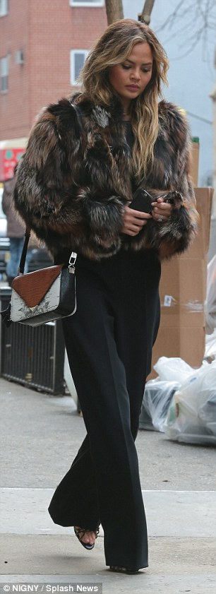 Smart luxe: The model teamed her fluffy jacket with chic high-waisted trousers