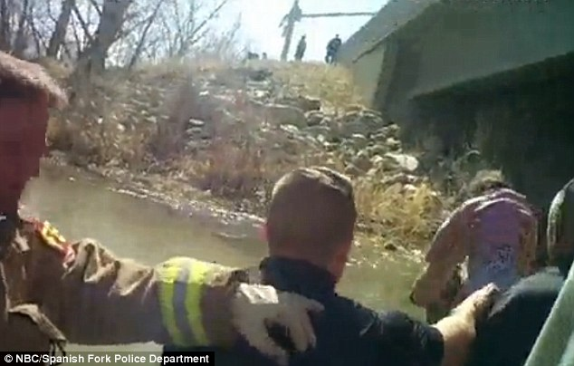 Life-saving rescue: The first responders were shocked to discover Lily hanging upside down in her car seat. They quickly freed the infant from the seat, before passing her cold body from one person to another (above)
