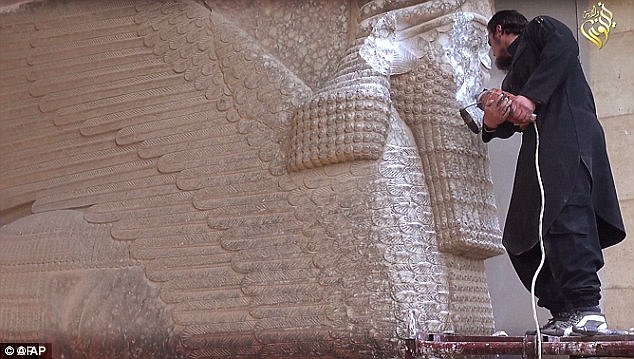 Real: An ISIS militant uses a power tool to destroy a 7th century winged-bull Assyrian protective deity. The statue is thought to have been one of only two genuine artifacts destroyed by ISIS in the video
