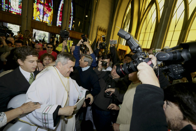 Outrage: Protesters, background left, shout as Rev. Juan Barros, center left,  enters the cathedral for the ceremony to assume as bishop in Osorno, southern Chile. Barros was ordained amid protests by sex-abuse victims who accuse him of covering up crimes his mentor  Rev. Fernando Karadima  whom the Vatican has sanctioned for abusing young boys