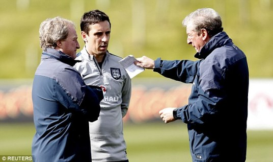 Hodgson talks with assistant manager Ray Lewington (left) and coach Gary Neville during the session