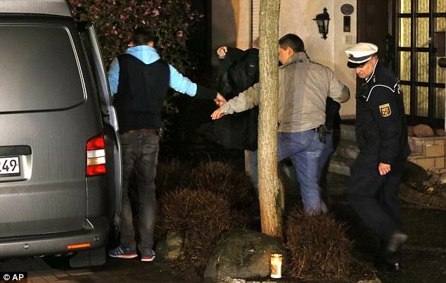 Una persona cubierta con una manta está dirigida por agentes de la policía de la casa se cree que es la casa familiar de Lubitz.  El jugador de 28 años de edad, se sobrentiende que dividir su tiempo entre la propiedad y su piso