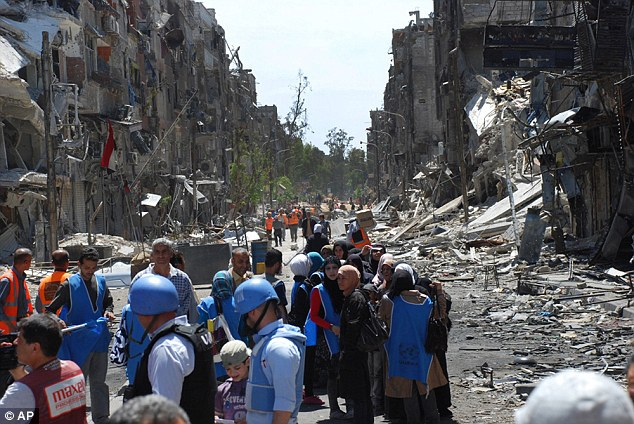 U.N relief workers with blue helmets and vests stand next of residents of the Yarmouk camp one year ago