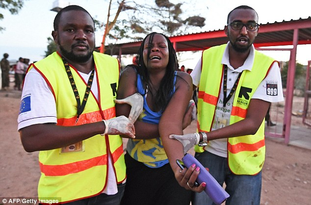 Distraught: Paramedics help a woman injured during the attack on the Garissa University College campus