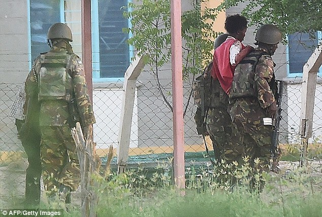 Safety: A student hostage is escorted out of Garissa University College after Kenya Defence Forces ended a siege by terrorist gunmen