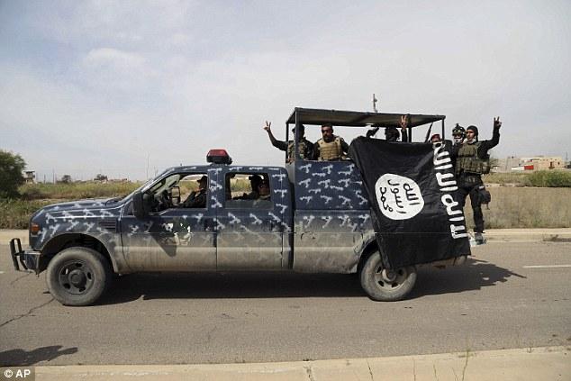 Derribando la bandera: milicianos chiíes Voluntarios han luchado junto a las tropas del ejército iraquí y se le atribuye un papel fundamental en el impulso ISIS de Tikrit y otras ciudades