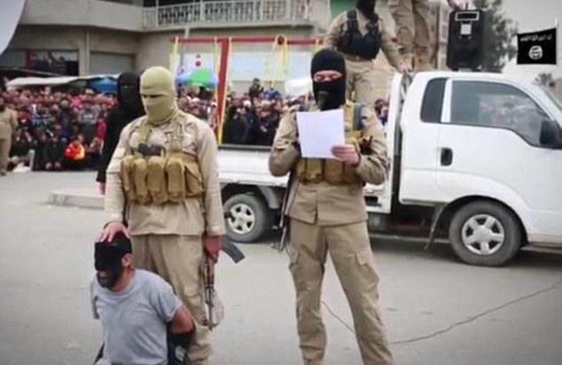 Condenado a la decapitación: Uno de los cuatro hombres que se ve con los ojos vendados y obligados de rodillas en el centro de Mosul, mientras que un militante enmascarado Estado Islámico lee los cargos en su contra