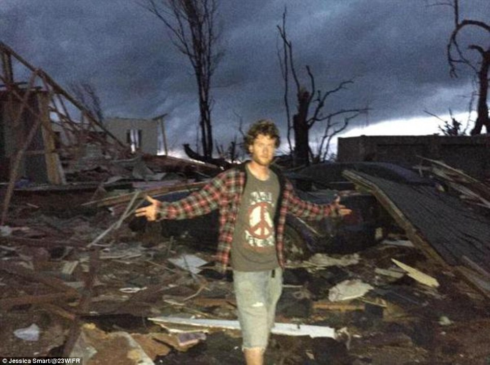 Jessica Smart captured this photo of a Fairdale resident posing in front of the wreckage. Every structure in the tiny community was destroyed