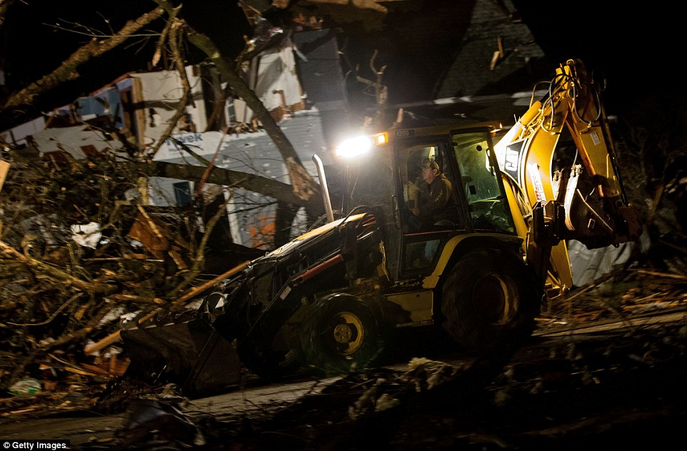Heavy duty: Crews work to clean debris on the IL-72 after a tornado came through the town earlier in the in Fairdale