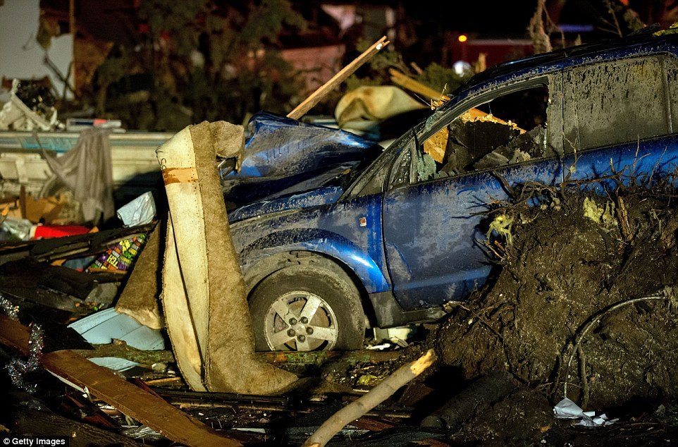 Shattered: A car is seen covered in mud with its side mirror missing and surrounded by tornado detritus
