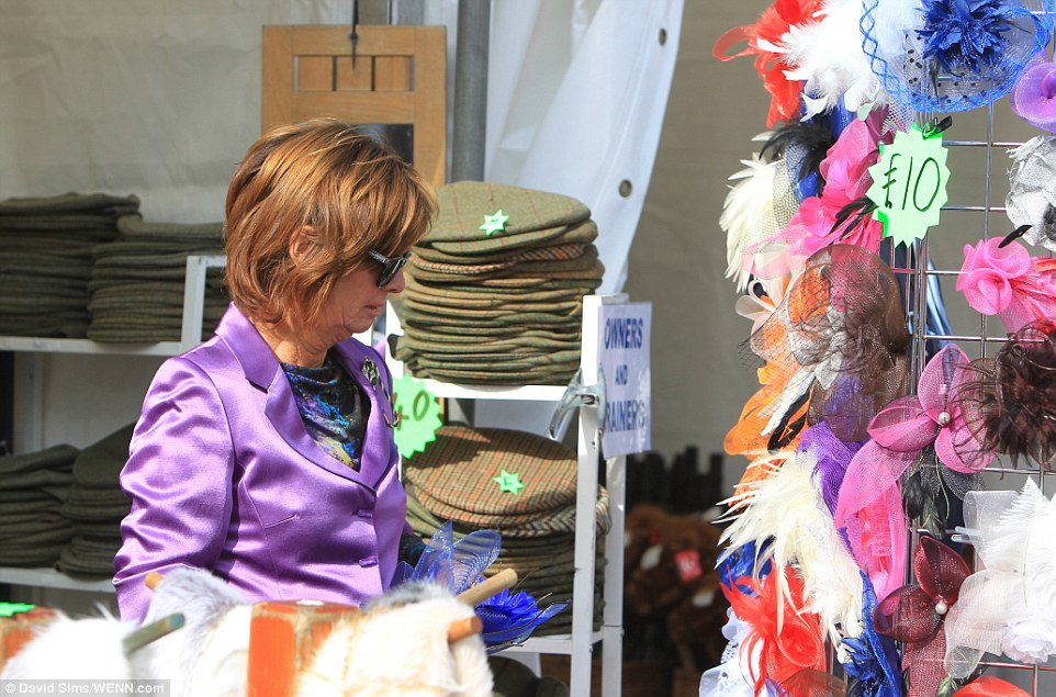 Making an entrance: A lady inspects a stall selling cut-price fascinators as she prepares to make her entrance
