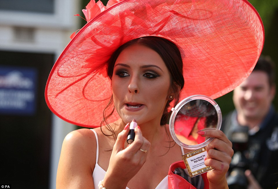 Final touches: A lady, who appears to have entered the racecourse's style competition, applies a final slick of lipstick