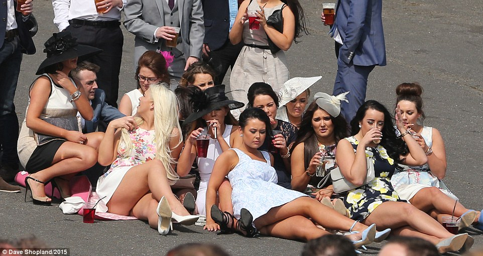 Sunbathing: Ladies huddle on a tarmac concourse as they enjoy a drink while topping up their tans