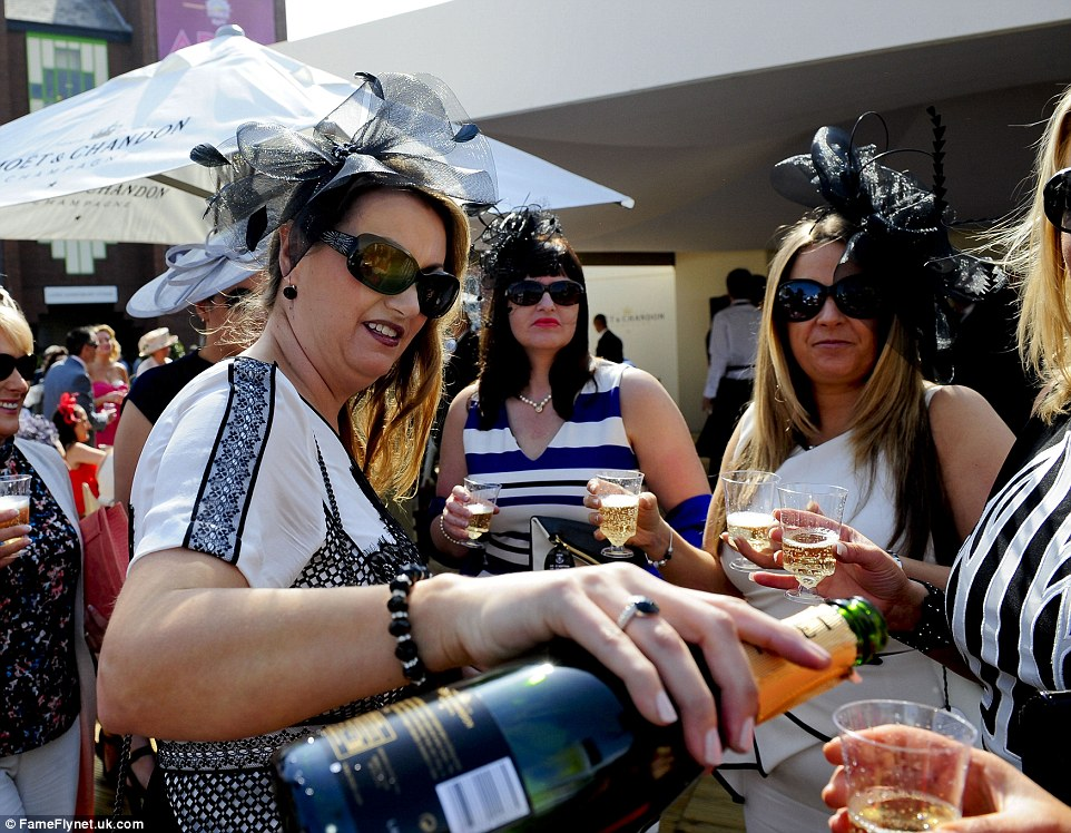 Party! Racegoers are clearly having a great time as they share a bottle of champagne while enjoying the sunshine