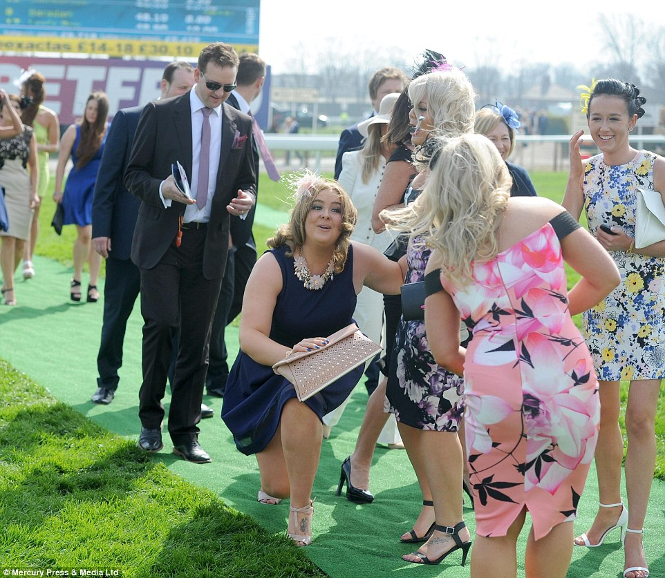 First faller! A lady's high heels prove unequal to the task of dealing with grass - but at least she's still smiling