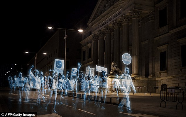 Ghostly gathering: Thousands of holograms march past theSpanish parliament in Madrid as part of a virtual protests against a new law banning demonstrators outside government buildings