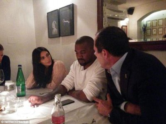 Original: In the original photo (pictured), posted to Mr Barkat's Twitter feed, Kim can be seen chatting with the mayor and Kanye. However, in the altered pictured, her face and body were obscured by a copy of the $692 bill