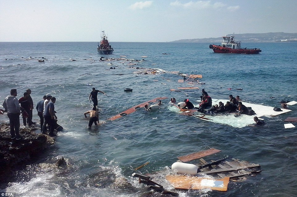 Rescue:The vessel capsized after hitting rocks off the coast, causing dozens of desperate migrants to fall in to the choppy waters with Greeks and holidaymakers watching on in horror