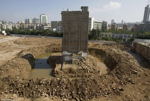 Owner Zhao Xing, 58, collects water near his partially demolished nail house at a construction site in Kunming, Yunnan province