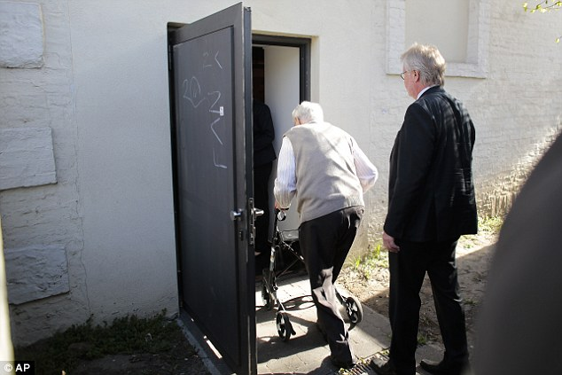 Groening uses a walking frame as he enters the back entrance of the court hall followed  by his lawyer Hans Holtermann