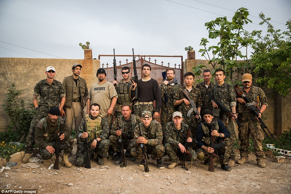 Legion: A group of international fighters pose for a photo in the outskirts of the north-western Syrian town of Tal Tamr earlier this week