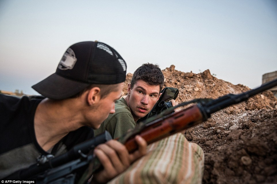 Fearless: Former US marines   Hewal Agir (right) and Hewal Agit (left) - aged 23 and 24 respectively - guard a position during clashes with ISIS
