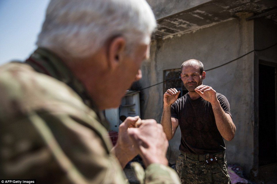 Practise: In one shot the 67-year-old Canadian fighter who goes by the name Heval Zinar and a 40-year-old British man nicknamed Heval Cudi are seen sparring and play fighting with one another under the blazing northern Syrian sun