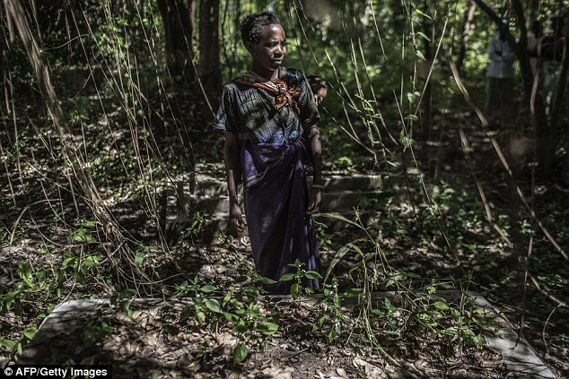 Village chief Mariam Witness stands in a graveyard where the grave of an albino person was recently desecrated. Body part traders are known to exhume graves in order to obtain body parts in the cruel trade