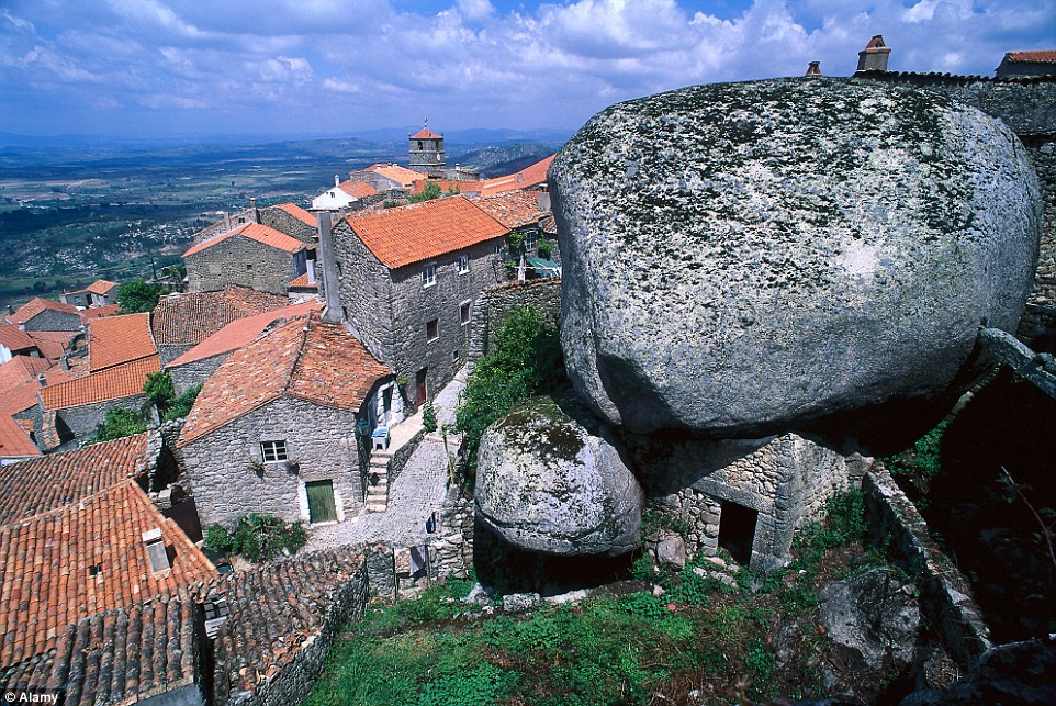 The village under a rock! Monsanto in Portugal has built its homes around the 200-tonne rocks in the area. Some of its 828 brave residents even sleep under gigantic boulders