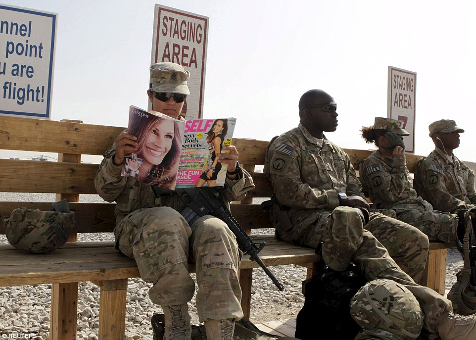 US Army soldier SSG Norma Gonzales of 426 Civil Affairs Battalion reads a magazine while waiting to be transported by helicopter to a base in Kandahar, southern Afghanistan in 2012