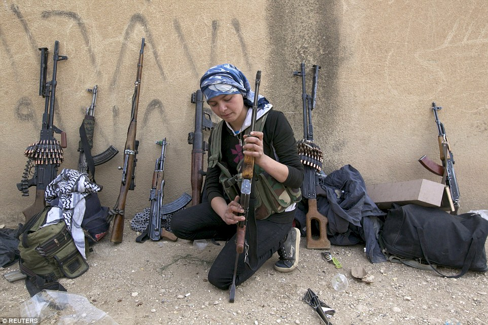 Weapons inspection: A Kurdish female fighter from Kurdish People's Protection Units (YPG) checks her gun near Ras al-Ain, in the province of Hasakah, Syria, after capturing the city from Islamist rebels in 2013
