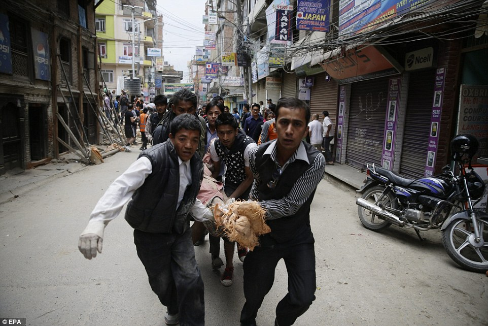 A group of men carry an injured person through the street after a powerful 7.8 magnitude earthquake struck Nepal causing massive damage in the capital Kathmandu