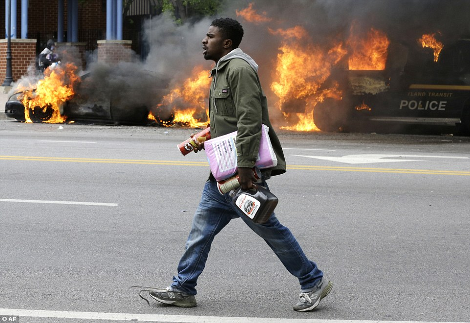 Shameless: A looter carries items from a store he has robbed as police vehicles burn outside Mondawmin Mall in the northwest side of Baltimore