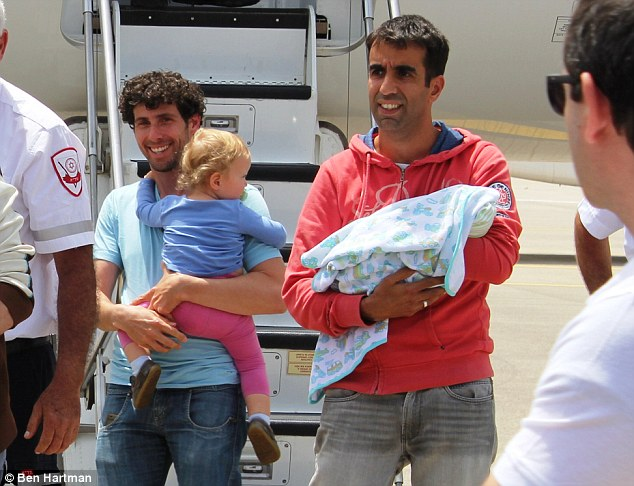 Joyful: An Israeli man and his partner are pictured carrying their two children - include a newborn baby born to a surrogate mother in the Nepalese capital of Kathmandu - after touching down at an airport in Israel