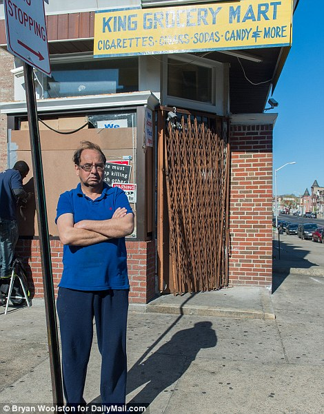 Rashad Kahn stands in front of his grocery mart that was damaged